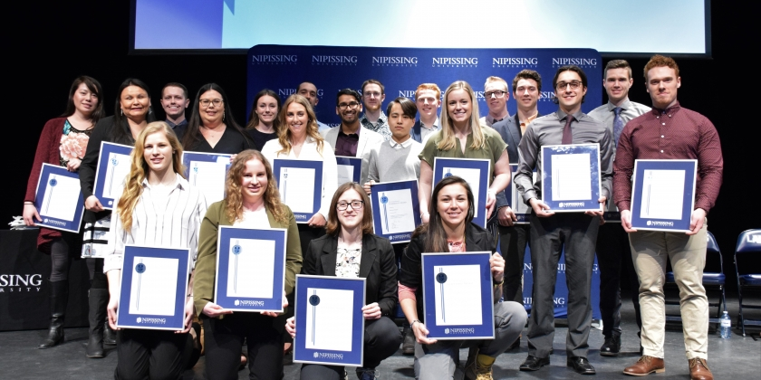 Group photo of 21 of the 25 Dave Marshall Leadership Award Recipients for 2019. In the photo the recipients are posing with their framed leadership awards.